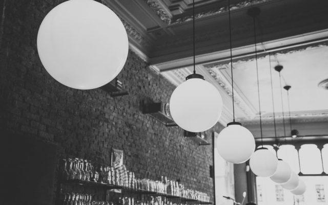 Barszene mit altem Mauerwerk, kugelförmigen Lampen und Stuck in schwarz weiß