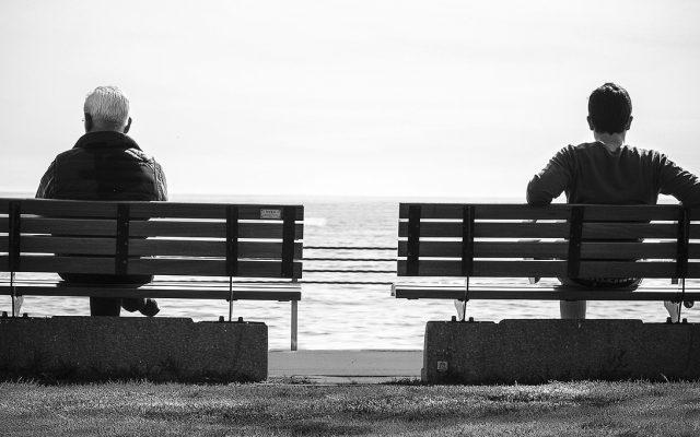 Zwei Bänke mit jeweils einem Mann mit Blick aufs Meer in schwarz weiß