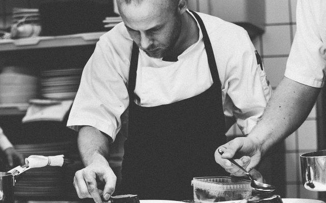 Chefkoch mit Schürze bei der Arbeit in schwarz weiß