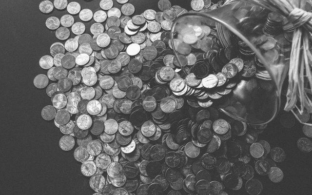 Aus einem Glas heraus gefallene Münzen liegen auf einem Tisch in schwarz weiß