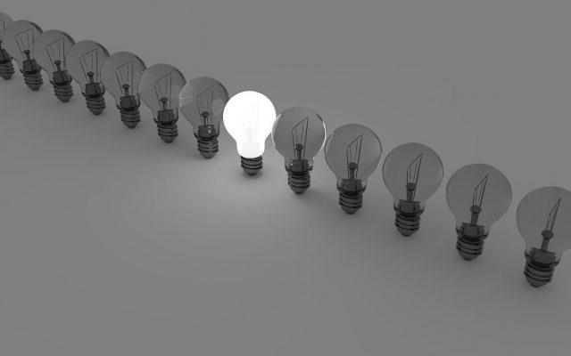 Glühbirnen aufgereiht mit einer brennenden Glühbirne in der Mitte in schwarz weiß