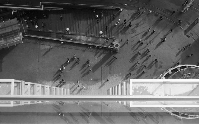 Blick von einem Gebäude nach unten mit vielen Menschen in schwarz weiß