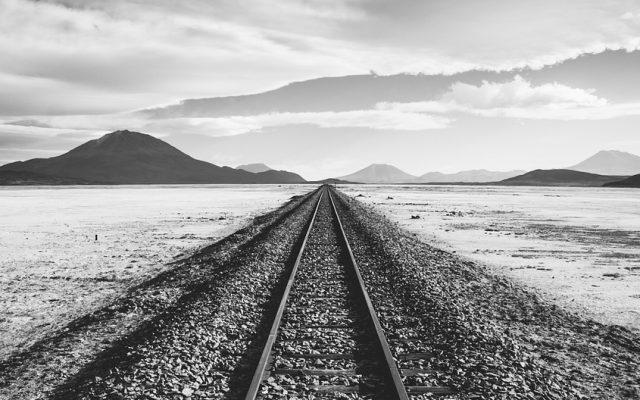 Verlassene kilometerlange Zugstrecke mit Bergen im Hintergrund in schwarz weiß