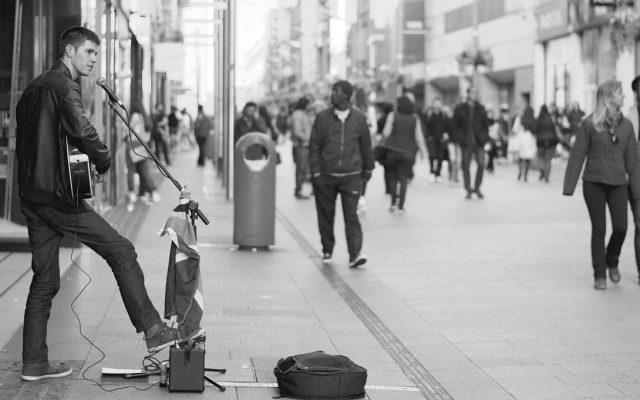Straßenmusiker mit Gitarre und Mikrofon in Fußgängerzone in schwarz weiß